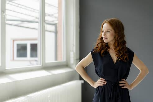 Portrait of redheaded businesswoman  in a loft looking out of window - KNSF06481