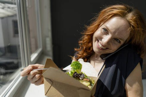 Portrait of happy redheaded businesswoman eating healthy takeaway food and talking on the phone - KNSF06487
