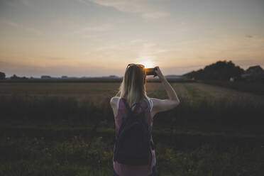 Woman taking a photo of sunset with her smartphone - CHPF00573