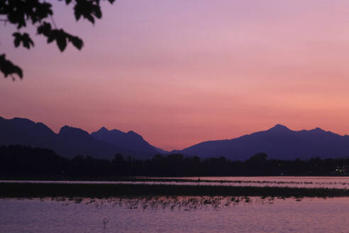 Scenic view of Forggensee lake and silhouette mountains against sky at sunset, Ostallgäu, Germany - JTF01303