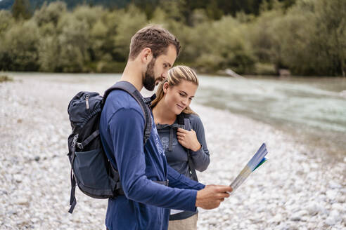 Young couple on a hiking trip reading map, Vorderriss, Bavaria, Germany - DIGF08255