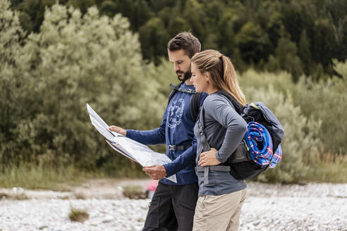 Young couple on a hiking trip reading map, Vorderriss, Bavaria, Germany - DIGF08258