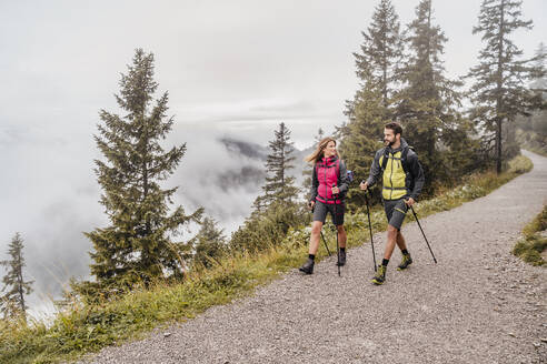 Young couple on a hiking trip in the mountains, Herzogstand, Bavaria, Germany - DIGF08261