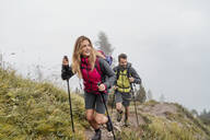 Young couple on a hiking trip in the mountains, Herzogstand, Bavaria, Germany - DIGF08267
