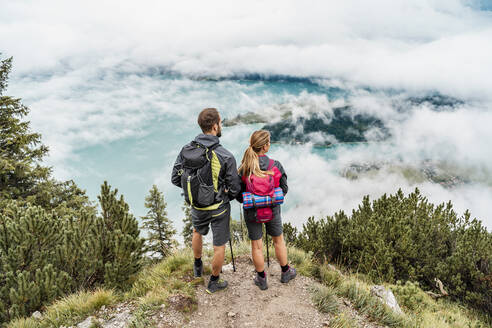 Young couple on a hiking trip in the mountains looking at view, Herzogstand, Bavaria, Germany - DIGF08270