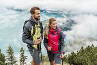 Confident young couple on a hiking trip in the mountains, Herzogstand, Bavaria, Germany - DIGF08273