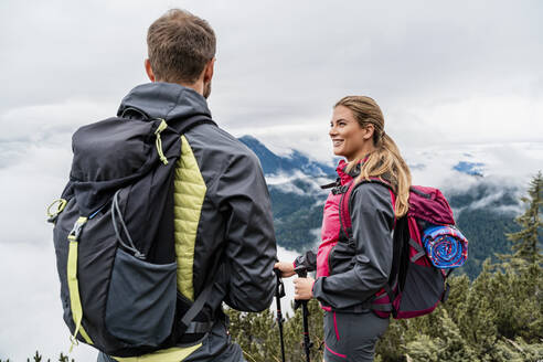 Smiling young couple on a hiking trip in the mountains, Herzogstand, Bavaria, Germany - DIGF08276