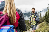 Smiling young couple on a hiking trip in the mountains, Herzogstand, Bavaria, Germany - DIGF08279
