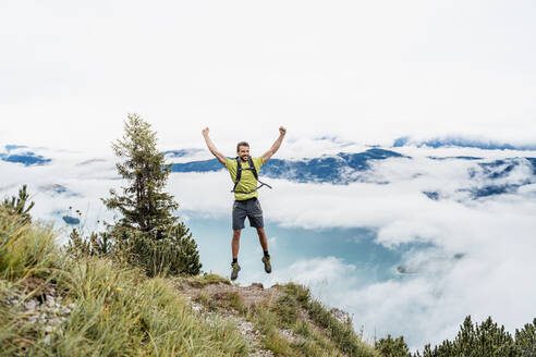 Happy young man with raised arms on a hiking trip in the mountains, Herzogstand, Bavaria, Germany - DIGF08288