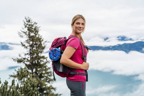 Confident young woman on a hiking trip in the mountains, Herzogstand, Bavaria, Germany - DIGF08291