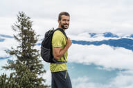 Portrait of smiling young man on a hiking trip in the mountains, Herzogstand, Bavaria, Germany - DIGF08294