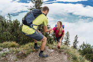Young man helping girlfriend on a hiking trip in the mountains, Herzogstand, Bavaria, Germany - DIGF08297