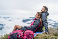 Affectionate young couple on a hiking trip in the mountains having a break, Herzogstand, Bavaria, Germany - DIGF08309