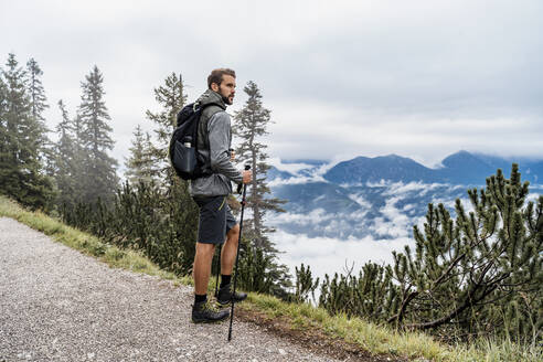Young man on a hiking trip in the mountains looking at view, Herzogstand, Bavaria, Germany - DIGF08312