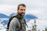 Portrait of confident young man on a hiking trip in the mountains, Herzogstand, Bavaria, Germany - DIGF08315