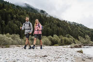 Young couple on a hiking trip at riverside, Vorderriss, Bavaria, Germany - DIGF08330