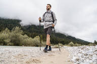 Young man on a hiking trip at riverside, Vorderriss, Bavaria, Germany - DIGF08333