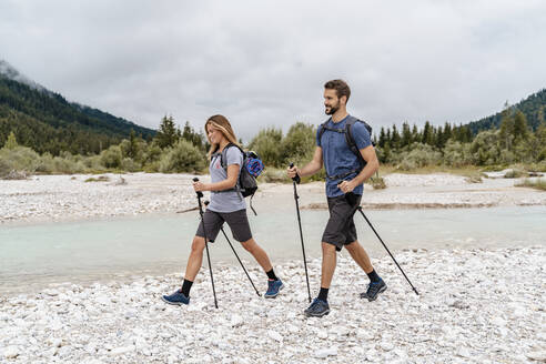 Young couple on a hiking trip at riverside, Vorderriss, Bavaria, Germany - DIGF08339