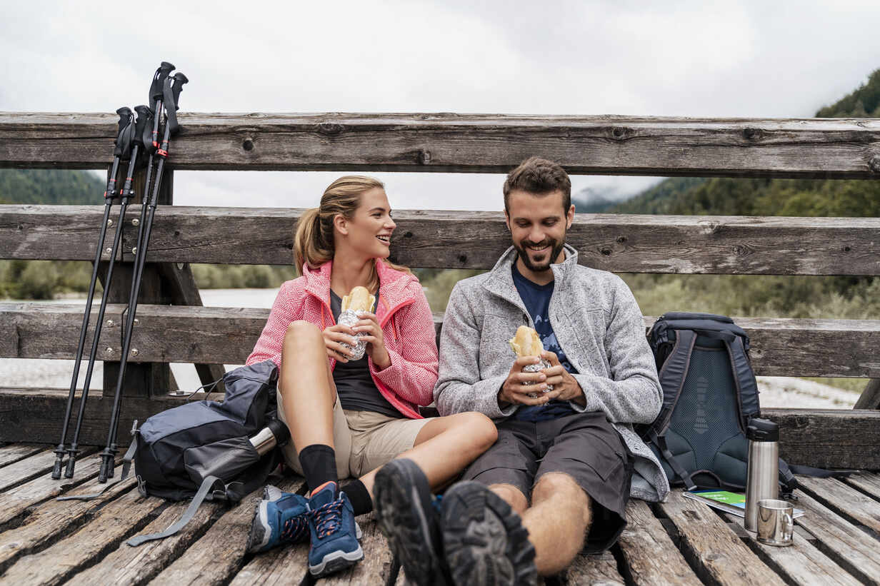 Young couple having a break on a wooden bridge during a hiking trip, Vorderriss, Bavaria, Germany - DIGF08351 - Daniel Ingold/Westend61