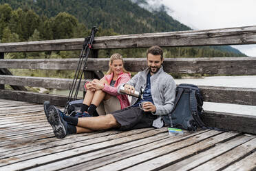Young couple having a break on a wooden bridge during a hiking trip, Vorderriss, Bavaria, Germany - DIGF08354