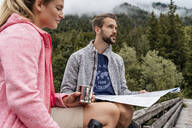 Young couple on a hiking trip with drink and map, Vorderriss, Bavaria, Germany - DIGF08360