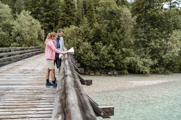 Young couple on a hiking trip reading map on wooden bridge, Vorderriss, Bavaria, Germany - DIGF08363