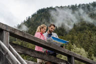 Young couple on a hiking trip reading map on wooden bridge, Vorderriss, Bavaria, Germany - DIGF08366