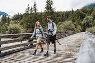 Young couple on a hiking trip walking on wooden bridge, Vorderriss, Bavaria, Germany - DIGF08369