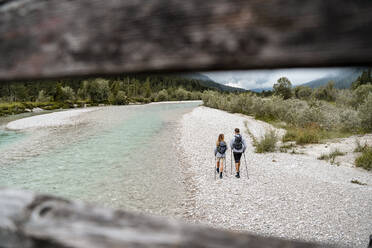 Young couple on a hiking trip walking at the riverside, Vorderriss, Bavaria, Germany - DIGF08372
