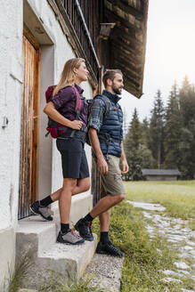 Young couple at a farmhouse during a hiking trip, Vorderriss, Bavaria, Germany - DIGF08375