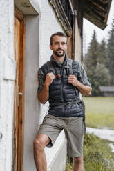 Young man at a farmhouse during a hiking trip, Vorderriss, Bavaria, Germany - DIGF08378