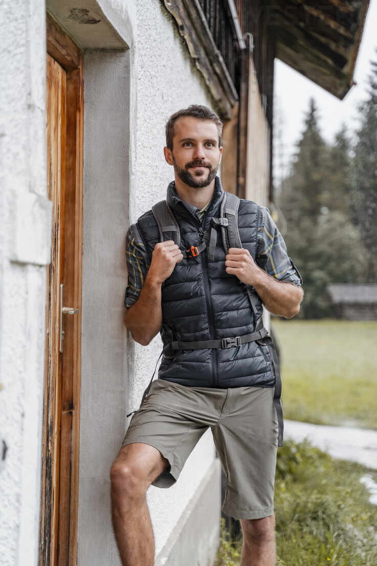 Young man at a farmhouse during a hiking trip, Vorderriss, Bavaria, Germany - DIGF08378 - Daniel Ingold/Westend61