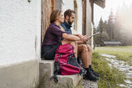 Young couple with map at a farmhouse during a hiking trip, Vorderriss, Bavaria, Germany - DIGF08381