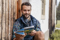 Smiling young man with map at a farmhouse during a hiking trip, Vorderriss, Bavaria, Germany - DIGF08387