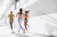 Rear view of three sporty young women running in the city - JCMF00199