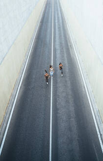 Top view of three sporty young women running on a street - JCMF00202