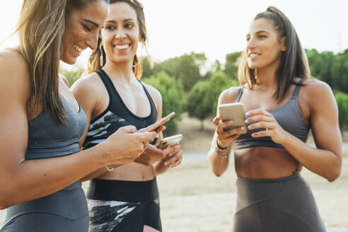 Three happy sportswomen using smartphones after workout - JCMF00205