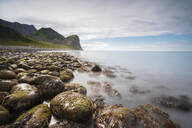 Rocks on the beach frame the calm clear sea, Unstad, Vestvagoy, Lofoten Islands, Norway, Scandinavia, Europe - RHPLF08808