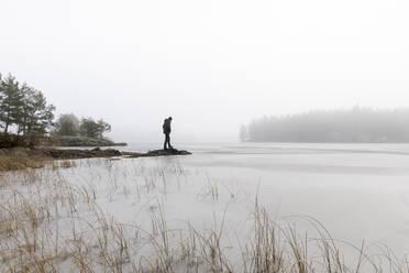 Man on rocks in frozen lake in Lotorp, Sweden - FOLF10933