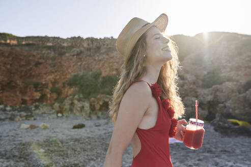 Happy young woman with a smoothie walking on the beach - IGGF01313
