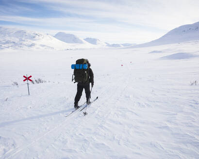 Woman skiing by markers on Kungsleden trail in Lapland, Sweden - FOLF11065