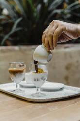 Hand pouring espresso into a glass - AFVF03930