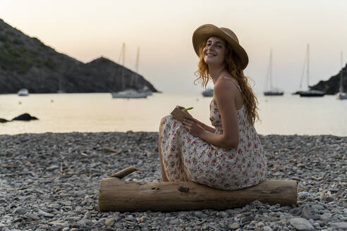 Young woman journalising, sitting on the beach at sunset - AFVF03935
