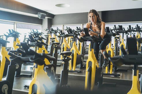 Woman in spinning class in gym - DLTSF00087