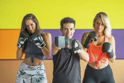Portrait of three athletes with boxing gloves posing in gym - DLTSF00090