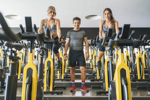 Portrait of training partners in spinning class in gym - DLTSF00105