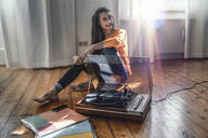 Young woman sitting on the floor at home with a record player - RIBF00988
