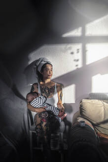 Tattooed young woman holding her baby at home enjoying the sunshine - RIBF01015