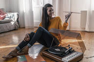 Smiling young woman sitting on the floor at home with record and record player - RIBF01024