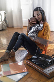 Mother with baby sitting on the floor at home with a record player - RIBF01027